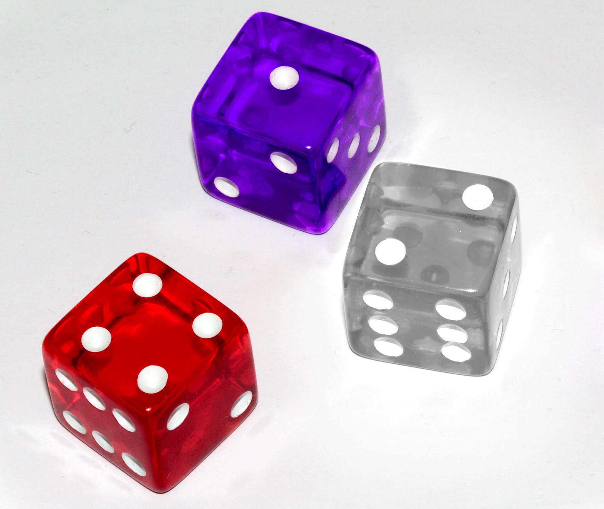 a photo of a red die, a purple die, and a silver die