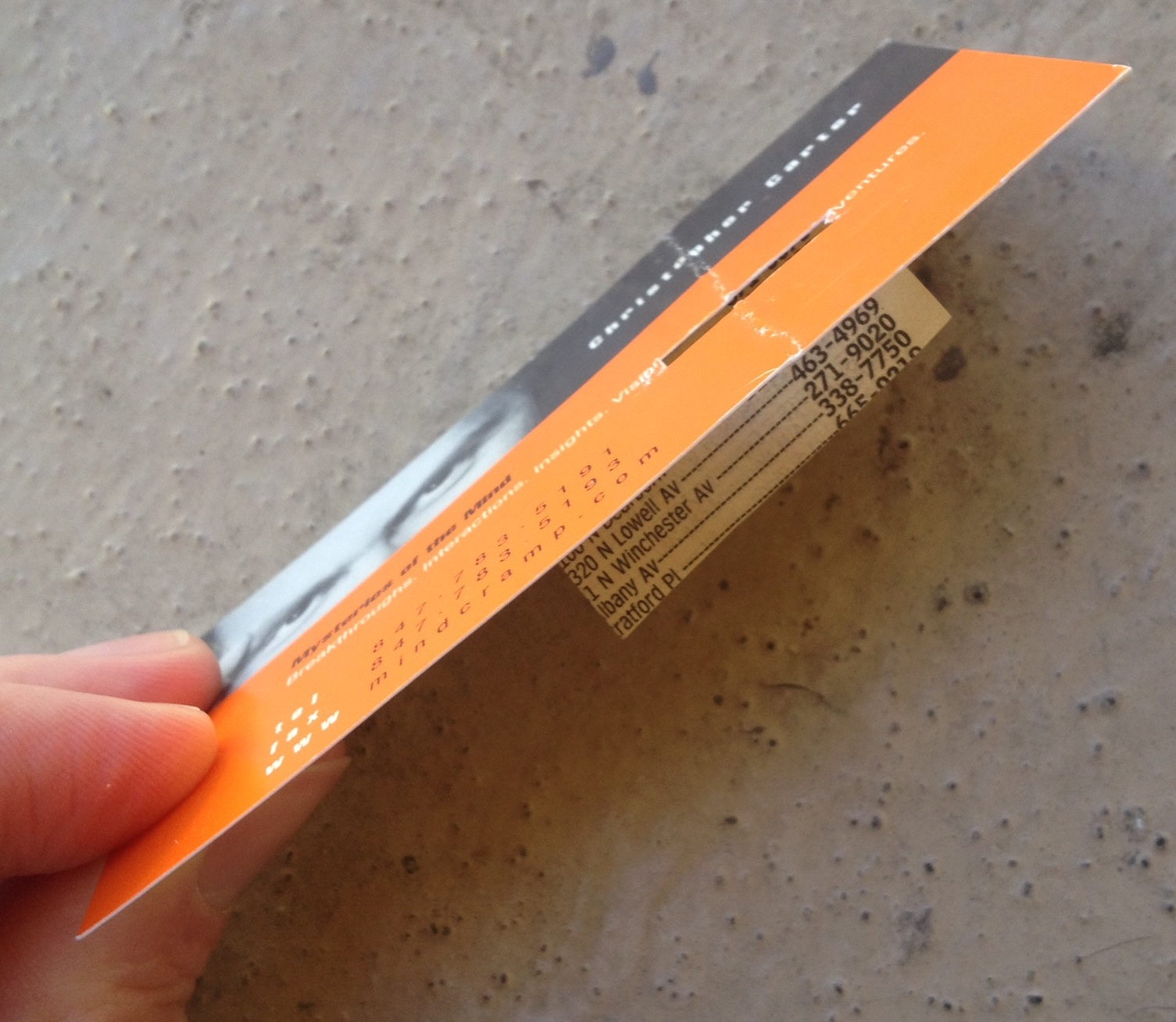 a photo of a business card with a piece of phone-book paper taped to the back of it