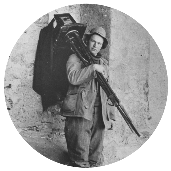 a tiny photo of Lisle Chandler Updike wearing a hat, set inside a circle, carrying a tripod