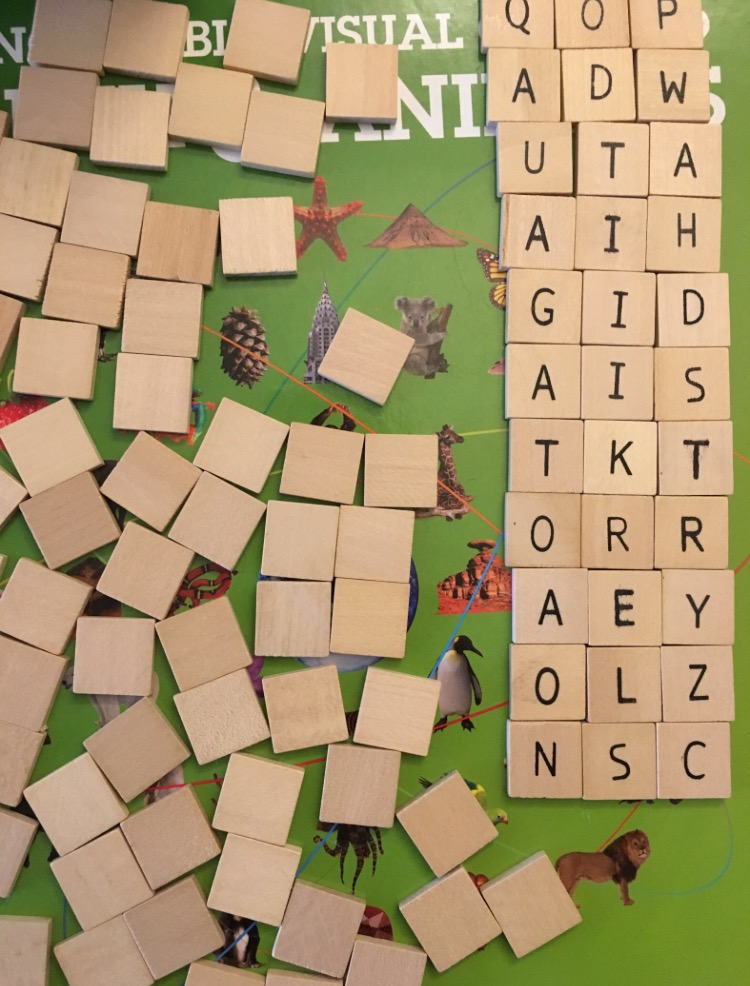 One hundred wooden letter tiles, most face down, and rows of three tiles face up, arranged in columns